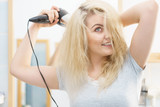 Blonde woman using hair dryer