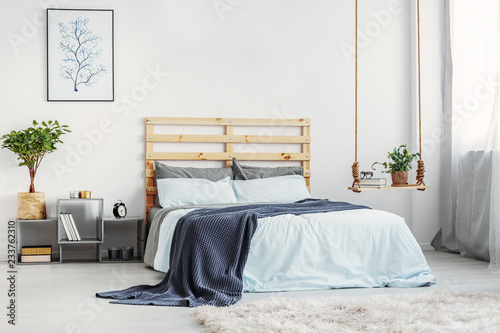 Leinwandbild Motiv Bright bedroom interior with king size bed with light blue bedding and warm blanket, copy space on white wall