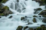 Langzeitbelichtung eines Gerbirgsflusses in Norwegen mit Felsen im Bachlauf, Norwegen
