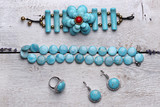 Natural turquoise stone jewelry.  Set with turquoise bracelet, ring, beads and earrings. Wood background