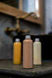 Spa cosmetics in plastic bottles on dark gray concrete table, bathroom interior. Beauty blogger, salon therapy, branding mockup, package, minimalism concept - 233789573