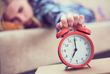 Young girl lies on the couch and stretches her hand to the red alarm clock to turn it off. Late wake up. - 233791954