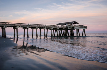 Wide angle view of the Tybee Island Pier in Georgia. Colorful sunset with pinks and purple colors in the sky