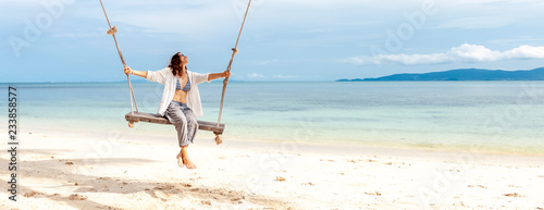 Beautiful young woman in a white shirt swinging on a swing on the beach, against the backdrop of a paradise landscape with turquoise water - 233858577