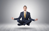 Businessman levitates and sitting in yoga position in an empty infinity space  - 233858955