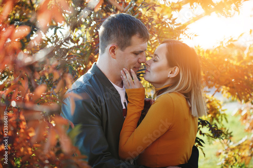 fototapeta na ścianę Young couple boy and girl hug and kiss in autumn park. Fall. Young Man and Woman outside. Happy family Concept. Yellow Trees and Leaves.