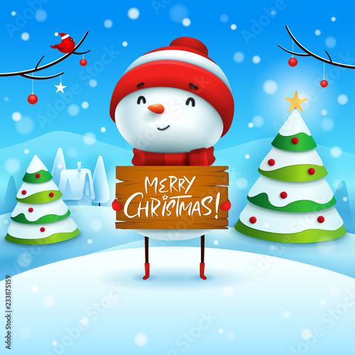 Wesołych Świąt! Rozochocony bałwan trzyma drewnianą deskę podpisuje wewnątrz Bożenarodzeniowego śnieżnego sceny zimy krajobraz.