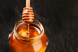 A bamboo honey dipper and a jar of organic honey on a dark background with copy space