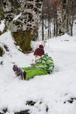 Young boy having fun lying in the snow - 233886344