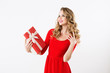 Excited cute girl in red dress holding present box.