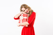 Beautiful cheerful woman in red dress with a gift over white background.