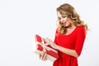 Beautiful cheerful woman in red dress with a gift over white.
