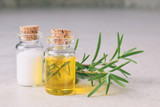 Rosemary essential oil in a small bottle and fresh twig on light background. Natural aroma cosmetic oil and salt - 233903531