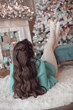 Leinwandbild Motiv Hairstyle. Pretty woman in fashionable blue knitted sweater. Beautiful brunette with long wavy hair style wears in warm woolen pullover lying on fur carpet by Christmas tree and xmas decorations.