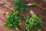 Bundles of dill and parsley on a wooden table - 233921580
