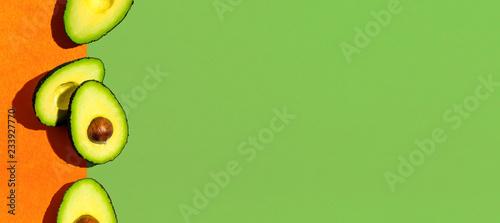 fototapeta na ścianę Fresh avocado pattern on a green and orange background flat lay