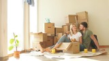 young couple with book sitting on bed while moving into new home - 233928567
