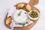 Camembert with olives and provencal herbs. Still Life with Camembert and Baguette