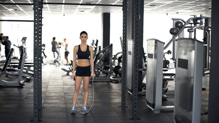 Active sport woman standing with jumping rope, gym workout, healthy lifestyle © motortion