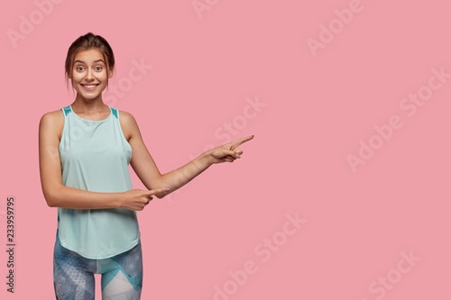 Leinwanddruck Bild Positive Caucasian woman with cheerful expression, dressed in casual vest and leggings, points aside with both index fingers, stands against pink background, has healthy lifestyle, likes sport