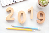 2019 wood letters, notebook paper and pencils on white marble table background, 2019 new year greeting card, banner, top view