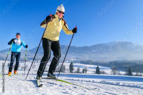 Leinwandbild Motiv Wintersportler beim Skaten im Chiemgau