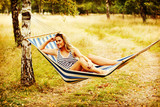 Young blonde woman resting on hammock - 234032505