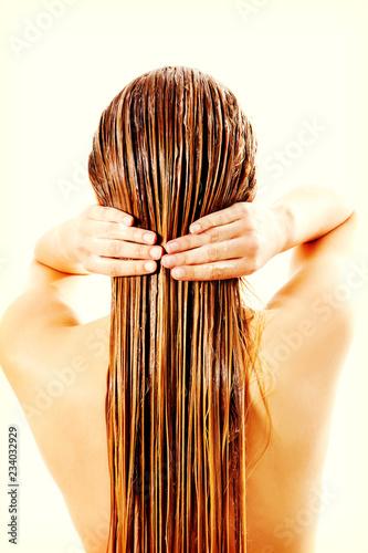 Leinwanddruck Bild Woman applying hair conditioner. Isolated on white.