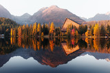 Picturesque autumn view of lake Strbske pleso in High Tatras National Park, Slovakia. Clear water with reflections of orange larch and high mountains on background. Landscape photography - 234044367