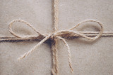 String or twine tied in a bow on kraft paper texture - 234069746