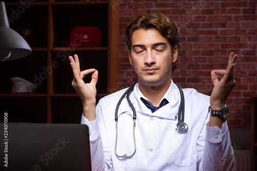 Leinwanddruck Bild Young handsome doctor working night time at the hospital