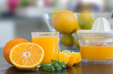 Glass and juicer with freshly squeezed orange juice with bowl of fruits on the background.