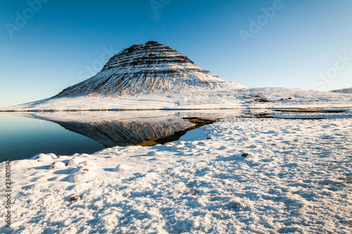 Kirkjufell view during winter snow which is a high mountain on the north coast of Iceland's Snaefellsnes peninsula, near the town of Grundarfjordur  - 234101147