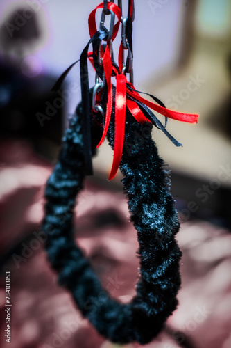 Soft fluffy handcuffs of black velvet hang on a chain above the bed. Attribute for love games and intimate fantasies.