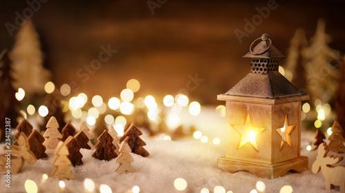 Leinwanddruck Bild Weihnachtliche Szene mit viel Holz im Laternenlicht
