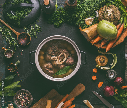 Cooked beef meat shin with bone in cooking pot on dark kitchen table background with low carb vegetables and spices ingredients for soup, top view. Meat broth or stock. Clean low-calorie food concept - 234113175