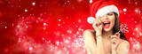 Christmas woman. Joyful model girl in Santa's hat with red lips and lollipop candy in her hand. Closeup portrait over red background - 234117358