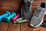 Sport accessories - colored dumbbells and sport shoes on wooden background