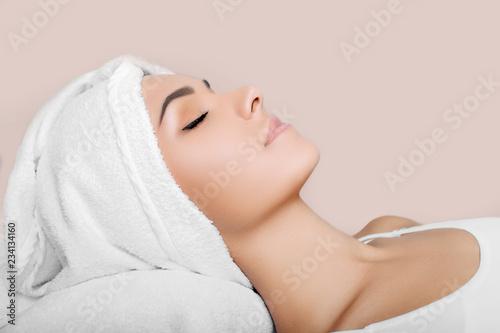kobieta z czystą świeżą twarz, z ręcznikiem na głowie, relaks po otrzymaniu leczenia spa. Kobiety o doskonałej skórze, cieszące się pielęgnacją skóry