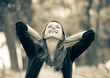 Beautiful girl in jacket sitting on grass in a park. Image in sepia color style