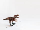 Dinosaur with present. Plastic toy with gift wrapped in silver paper. White background with star confetti. Place for text.