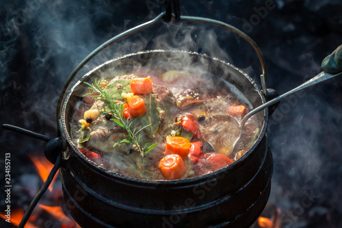 Hot and yummy hunter's stew on bonfire - 234155713