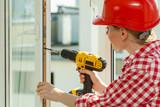 Woman using drill on window - 234157564