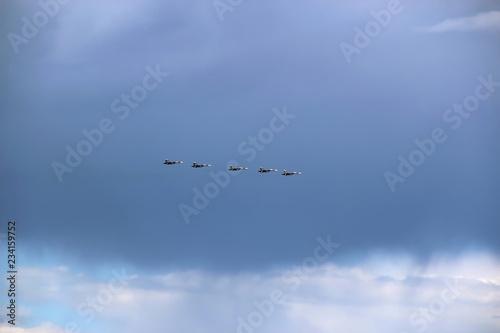 fototapeta na ścianę five jet fighters in the sky against a rain cloud background