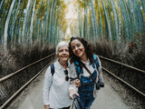 .Mother and daughter touring Japan and taking a picture together. Visiting the bamboo forest located in Arashiyama, Kyoto. Lifestyle. Travel photography. © lubero