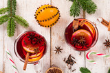 Christmas hot mulled wine with spices on wooden background.