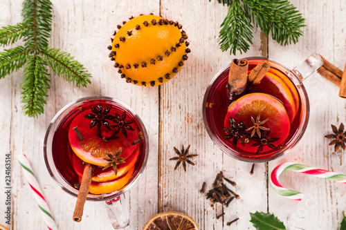 Leinwanddruck Bild Christmas hot mulled wine with spices on wooden background.