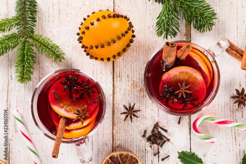 Leinwandbild Motiv Christmas hot mulled wine with spices on wooden background.