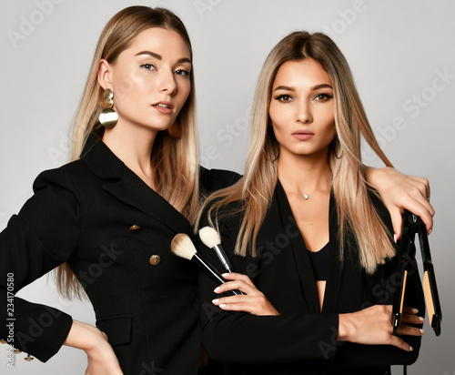 Leinwandbild Motiv Two young beautiful european makeup artists friends or girlfriends women in dresses
