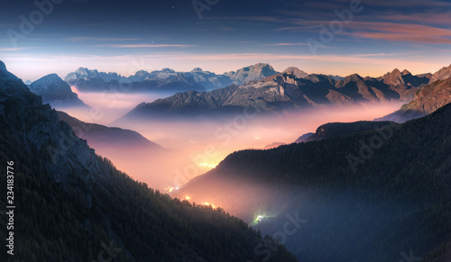 Leinwandbild Motiv Mountains in fog at beautiful night in autumn in Dolomites, Italy. Landscape with alpine mountain valley, low clouds, forest, colorful sky with stars, city illumination at dusk. Aerial. Passo Giau